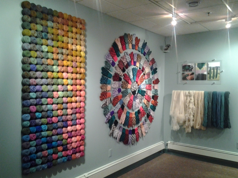 Skeins of natural wool hanging, dyed wool in balls on the wall and a Newfoundland mitten star burst. Great exhibit of Newfoundland hand made crafts.