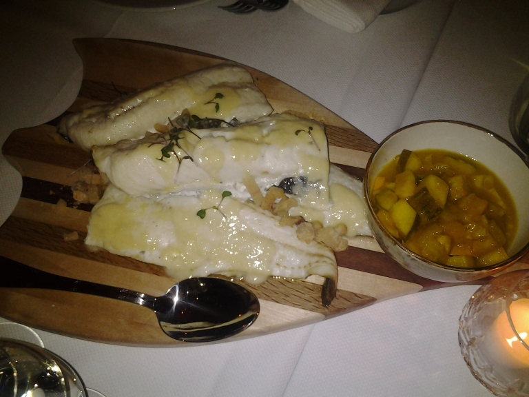 Roasted cod with drawn butter, scrunchins and mustard pickles on a split fish cutting board.