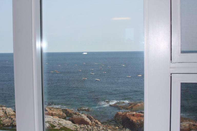 Floor to ceiling windows provide view of icebergs and punts. From Room 15, Fogo Island Inn. Photo credit, Tom Curran.